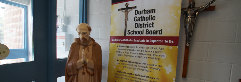 Stand up sign stating the Catholic Graduate Expectations beside a statue of St. Isaac Jogues.